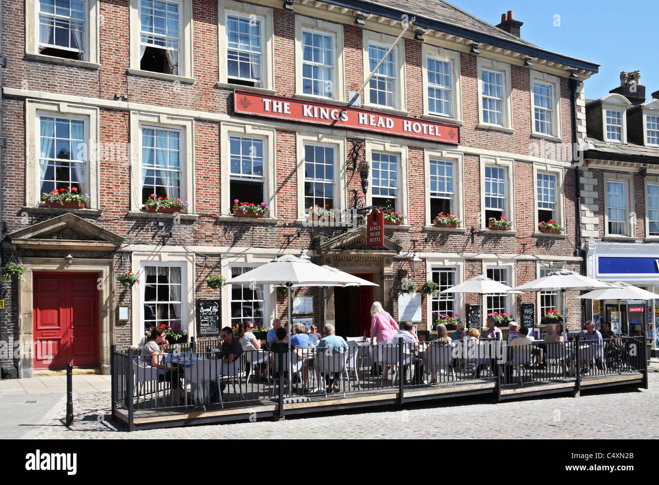 People dining outside the Kings Head Hotel in Richmond, Yorkshire, England, UK - Stock Image