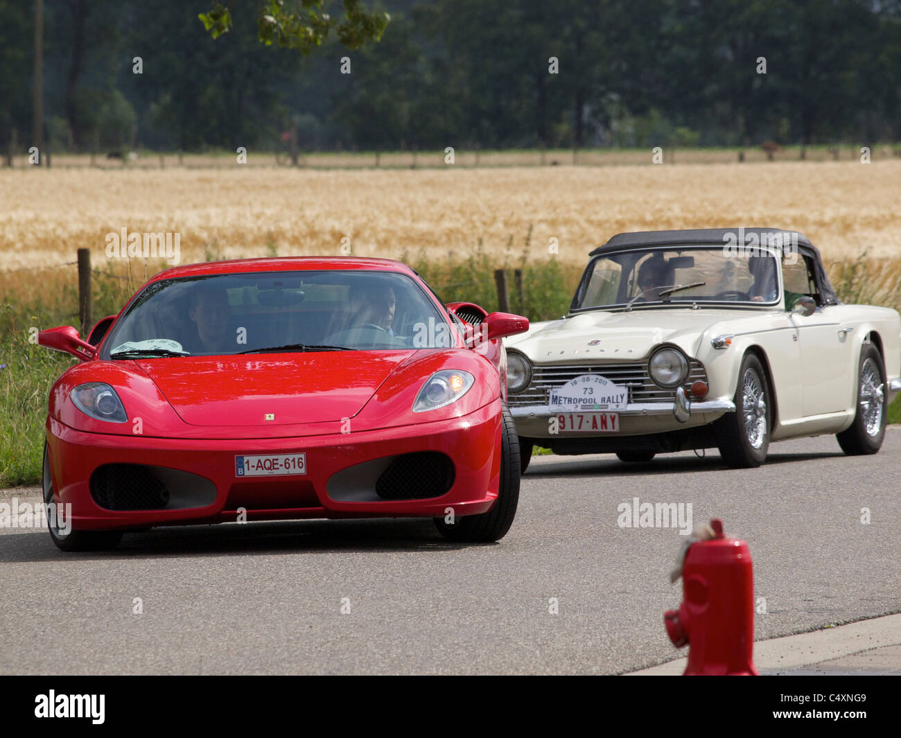 Modern Ferrari F430 and vintage Triumph TR4A sportscars at a classic car rallye in Belgium - Stock Image