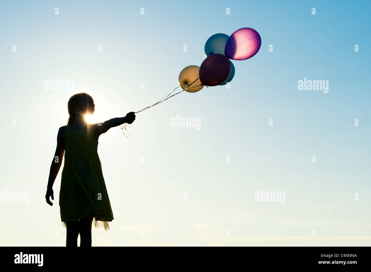 Silhouette of a young girl holding coloured balloons at sunset Stock Photo