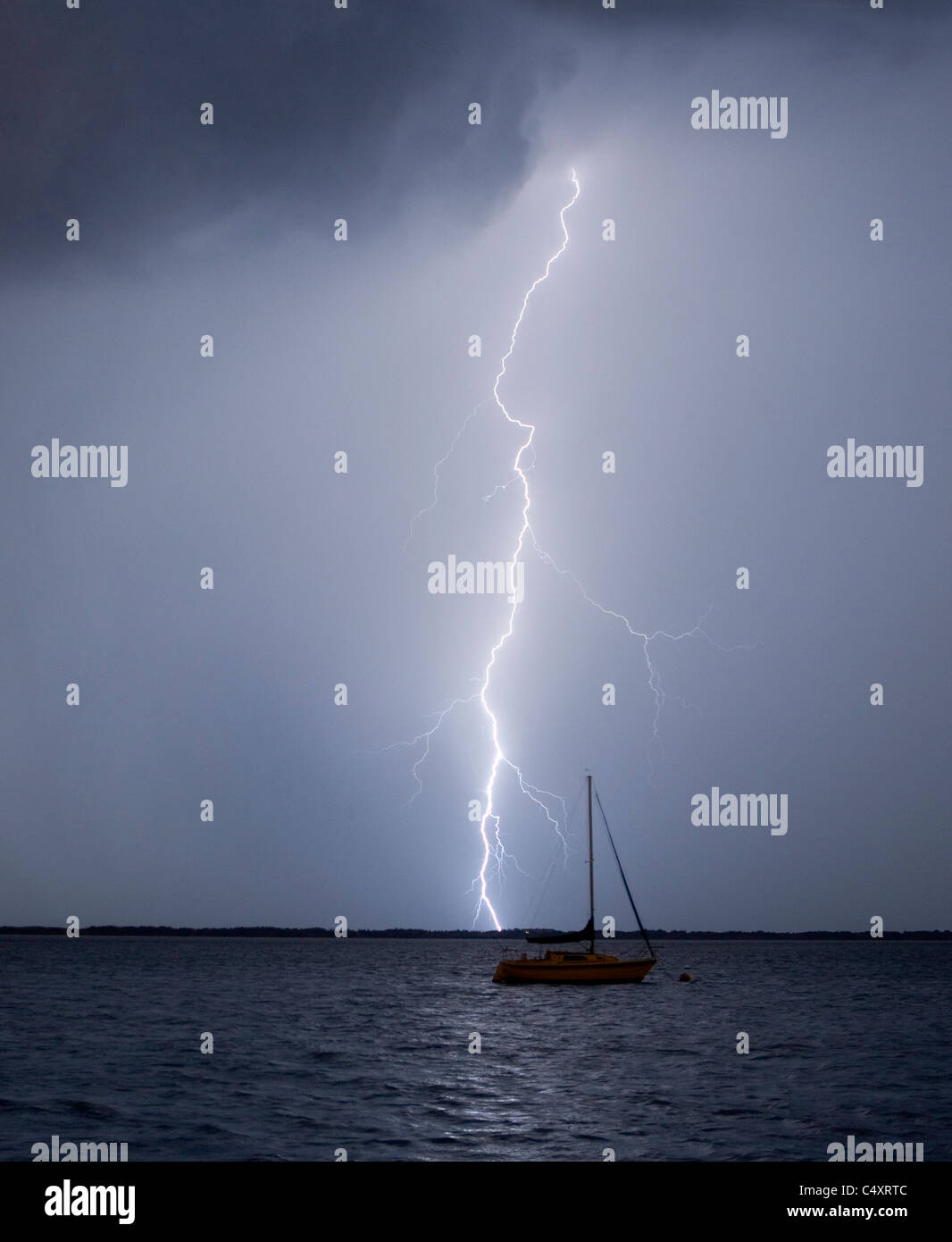 A lightning strike near a moored sailboat. - Stock Image