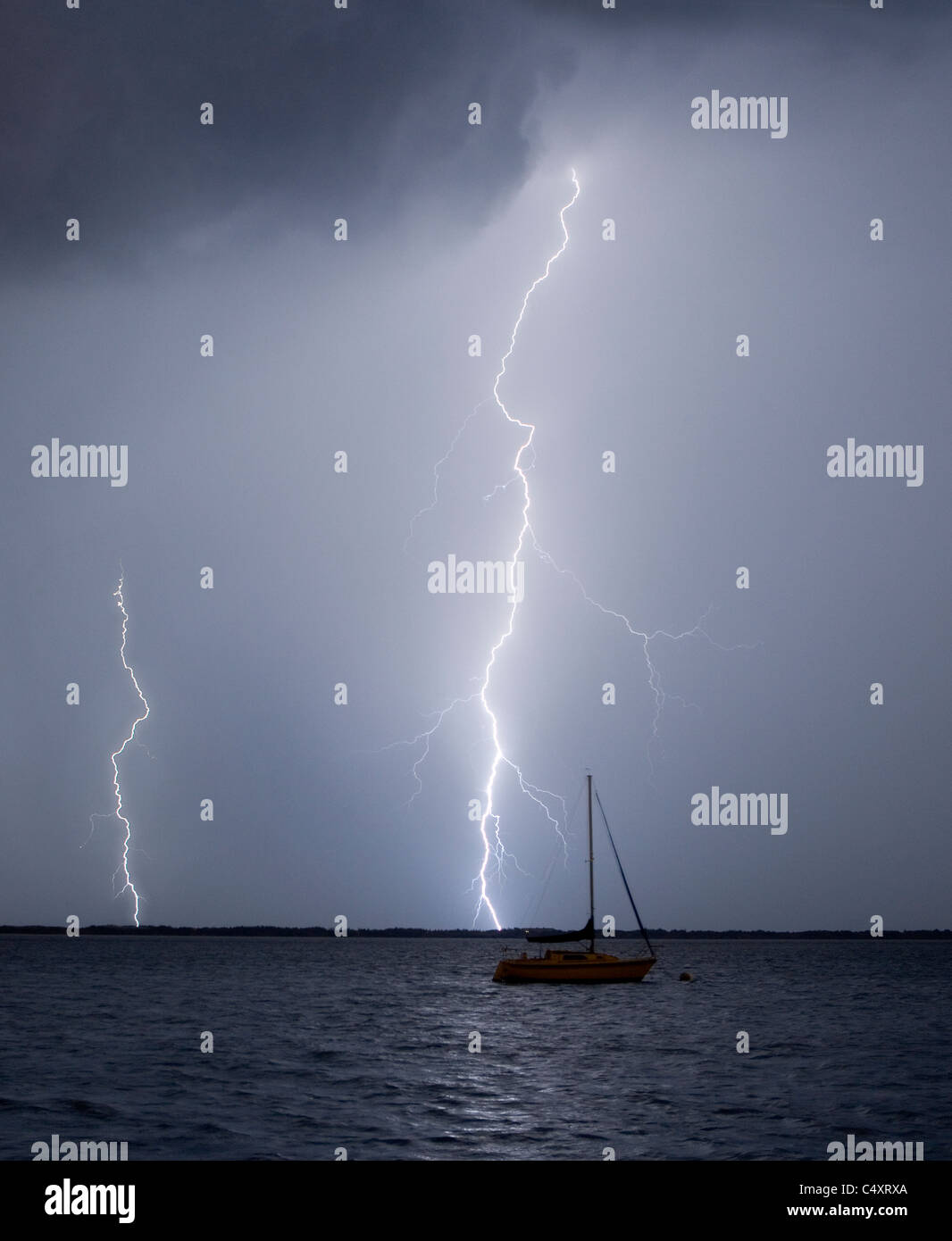 A lightning strike near a moored sailboat - Stock Image