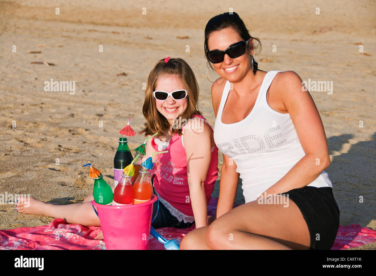 A bucket filled with sodas and their umbrella straws sits in front of a young girl and her adult female friend at - Stock Image