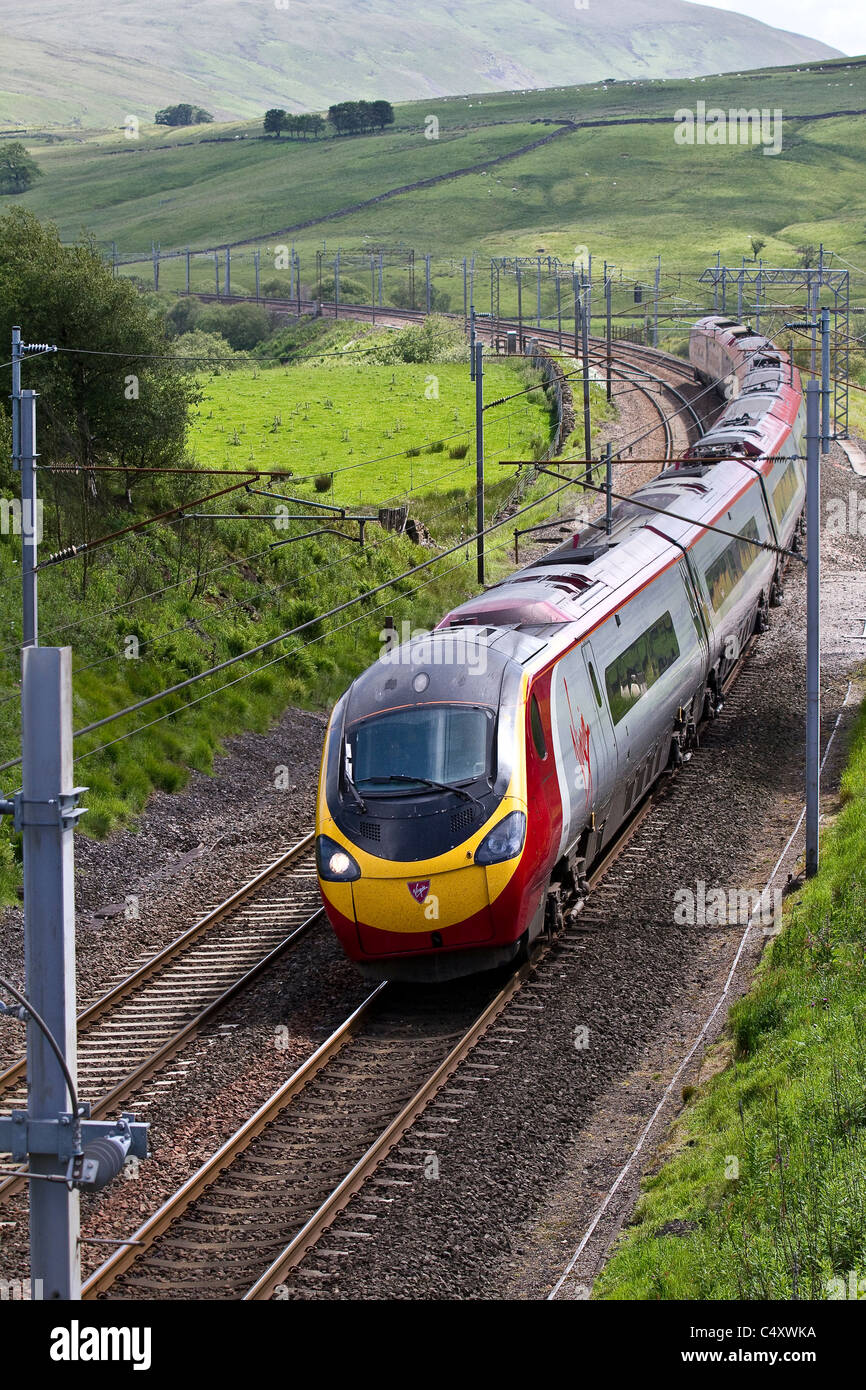 Power lines, and gantries for electric trains British Railways  Virgin Pendolino Train at Shap. West Coast Line, Stock Photo