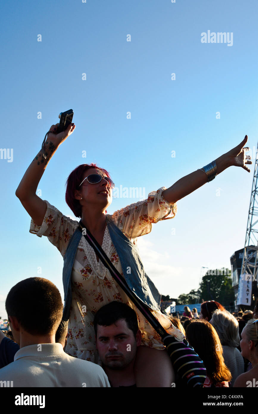 A woman high on a mans shoulders during the Hard Rock Calling 2011 Music Festival, Hyde Park on 25th June 2011. - Stock Image