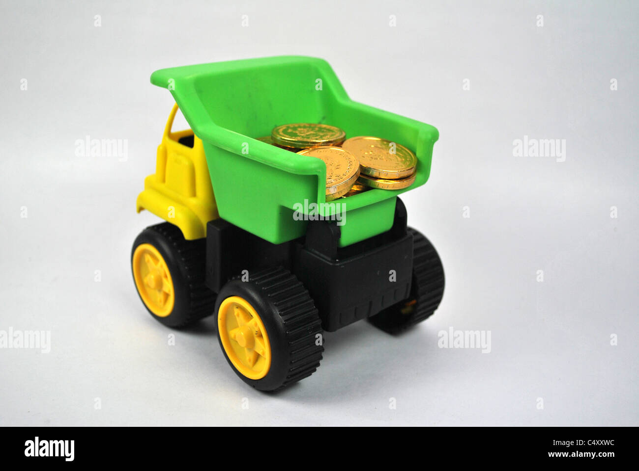 toy playful truck lorry mobile auto wealth money gold coin silo cut out cut-out white back ground isolated yellow - Stock Image