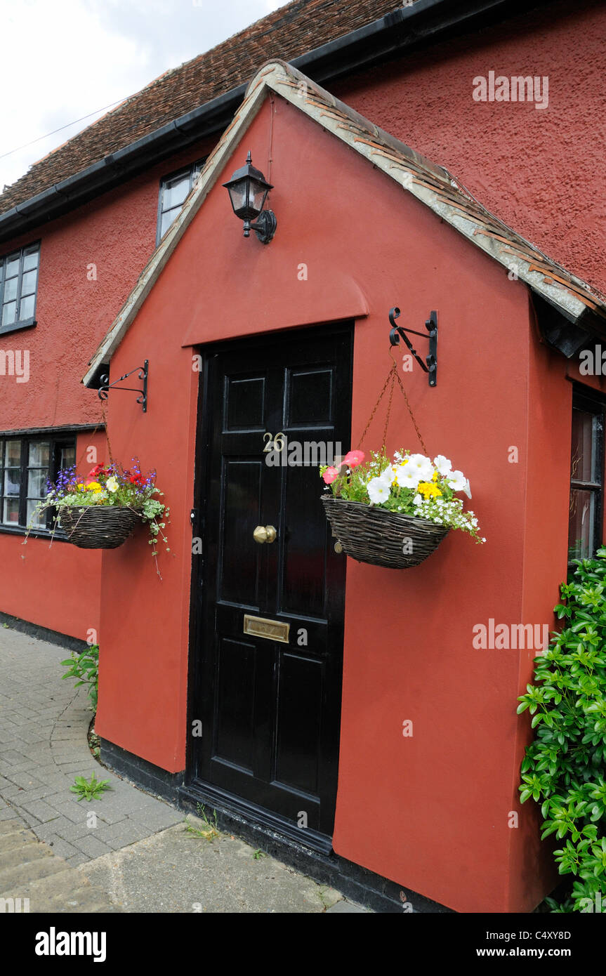 Hanging baskets outside the door of terracotta painted house or cottage Braughing Village Hertfordshire London England - Stock Image