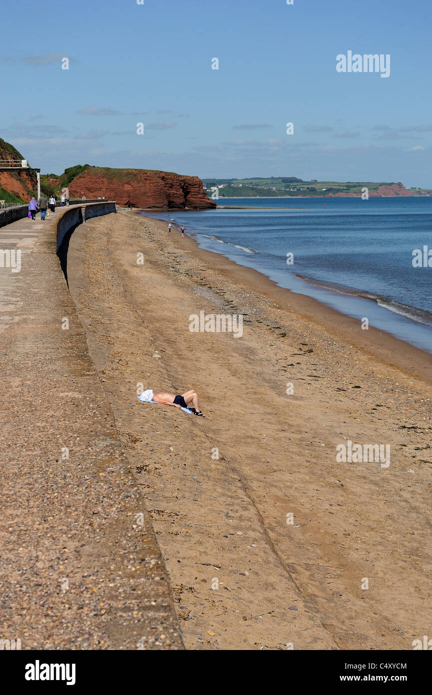 lone man sunbathing on dawlish beach devon england uk - Stock Image
