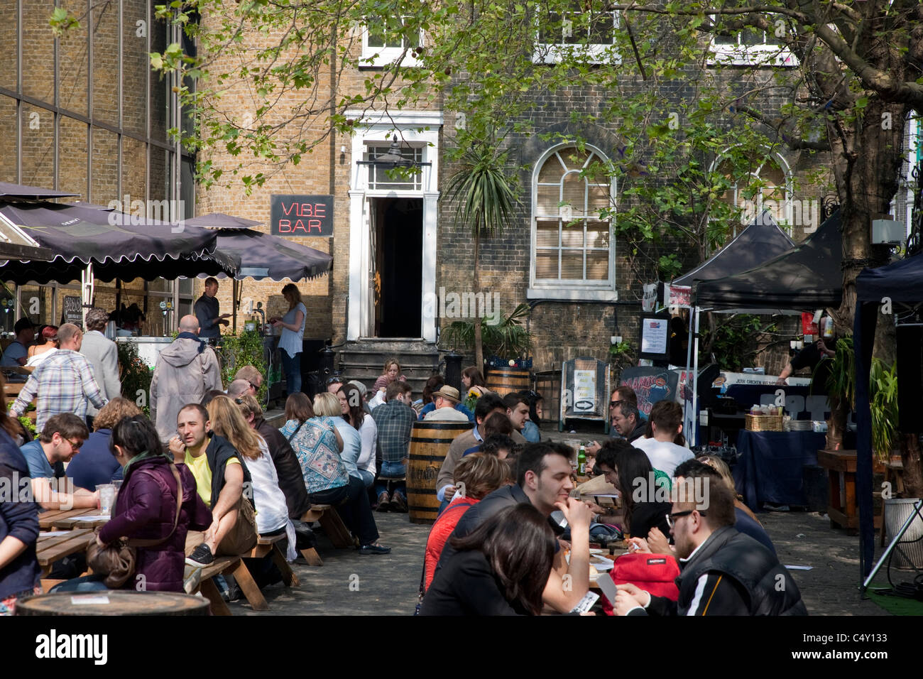 People Eating and Drinking in the Beer Garden in the Vibe Bar, Brick Lane, London - Stock Image