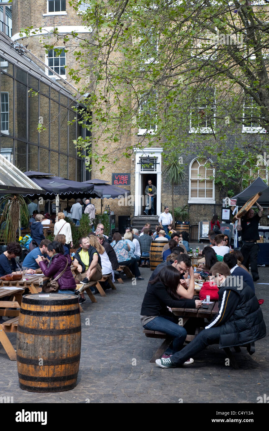 People Eating and Drinking in the Beer Garden of the Vibe Bar, Brick Lane, London, England, UK - Stock Image