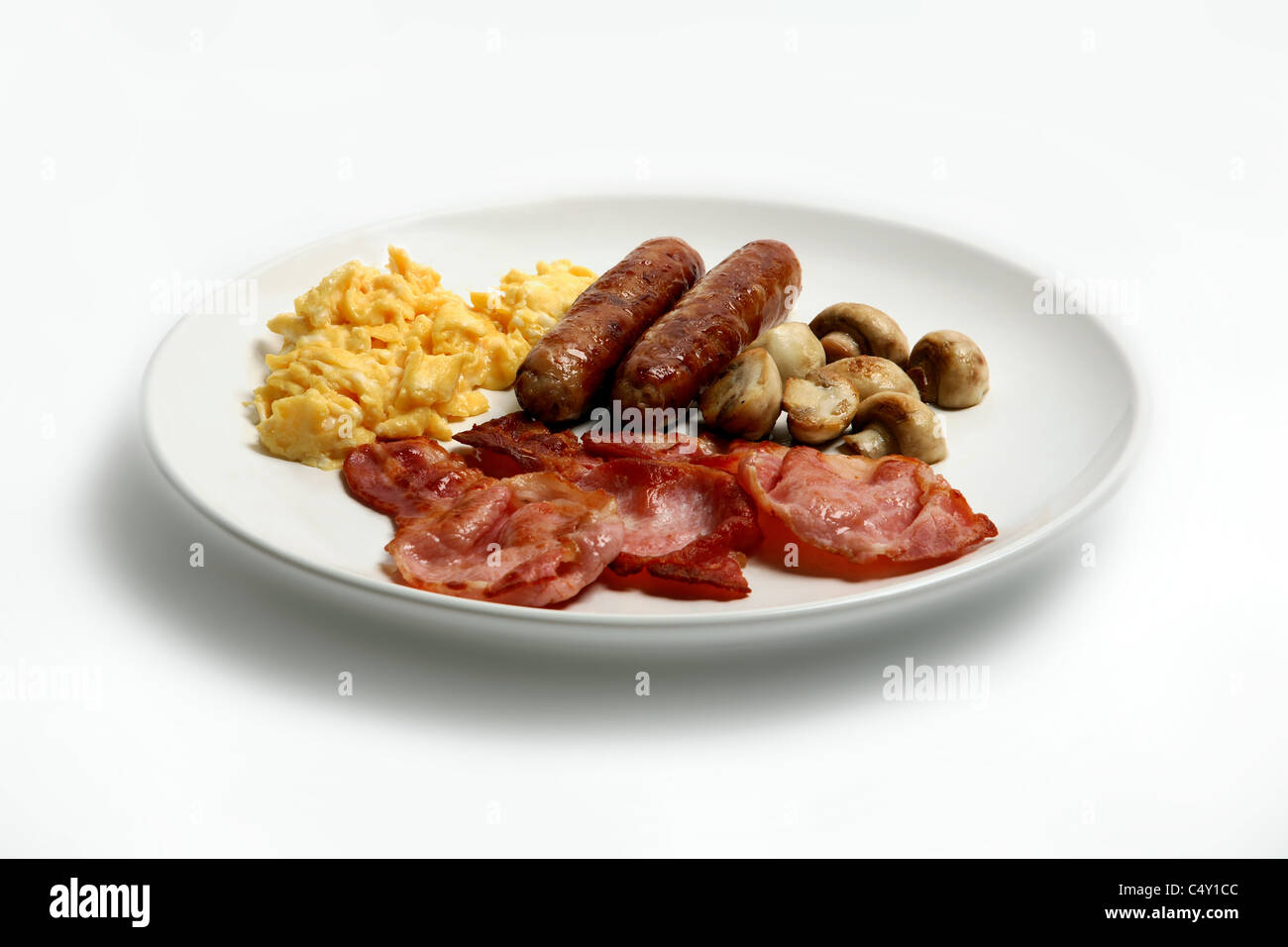 Sausage, bacon, mushrooms and scrambled egg on a white plate - Stock Image