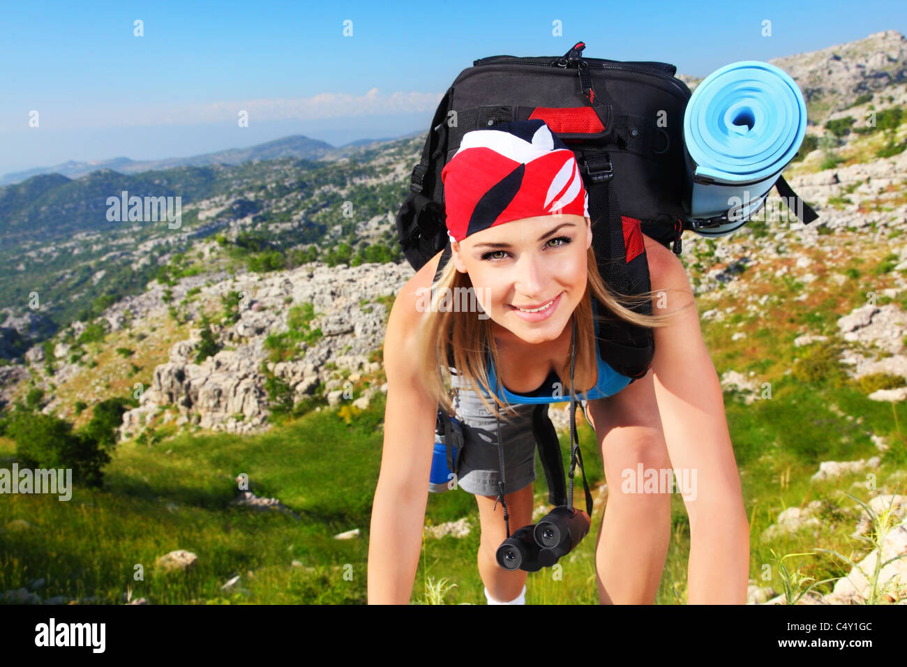 Traveling girl with backpack hiking in the mountains, freedom concept - Stock Image