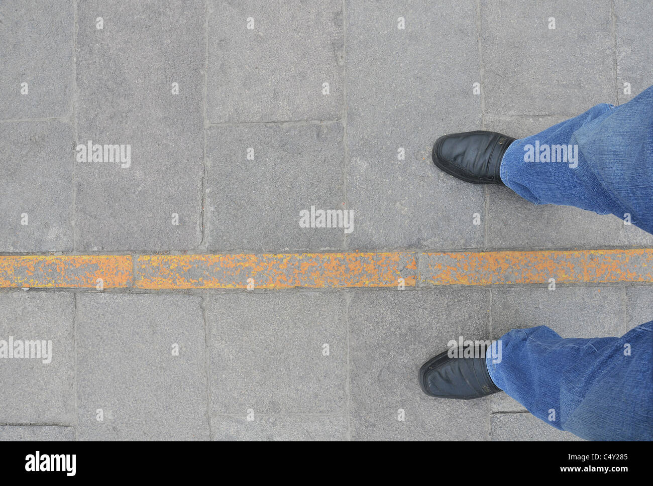 Straddling the equator, one foot in the northern hemisphere, one foot in the southern hemisphere, Mittad del Mundo - Stock Image