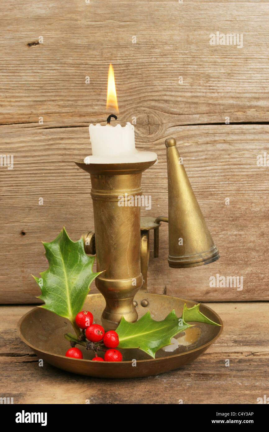 Brass candlestick with holly and burning candle against old wood - Stock Image