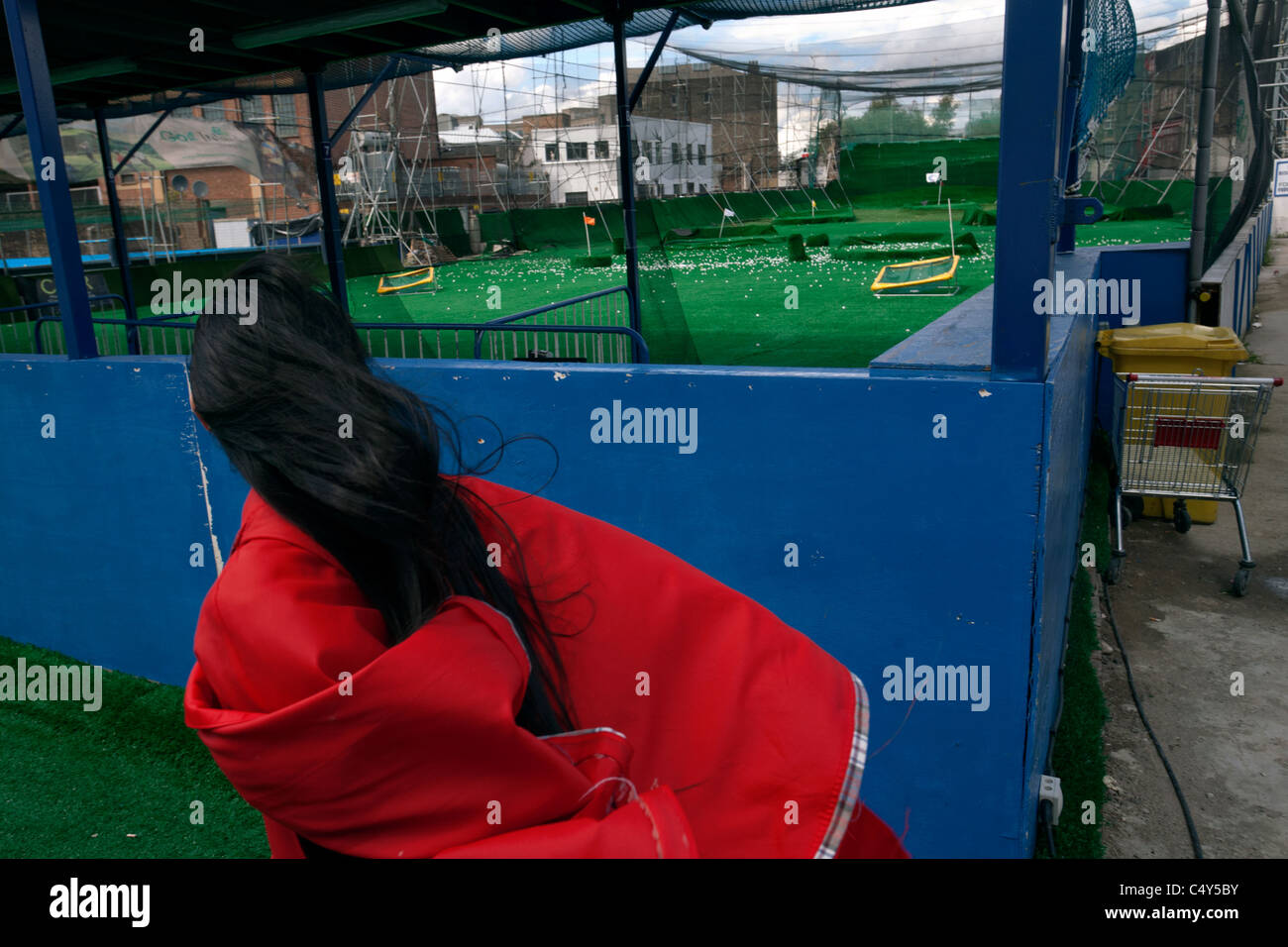 woman in red cloak at golf driving range in london - Stock Image