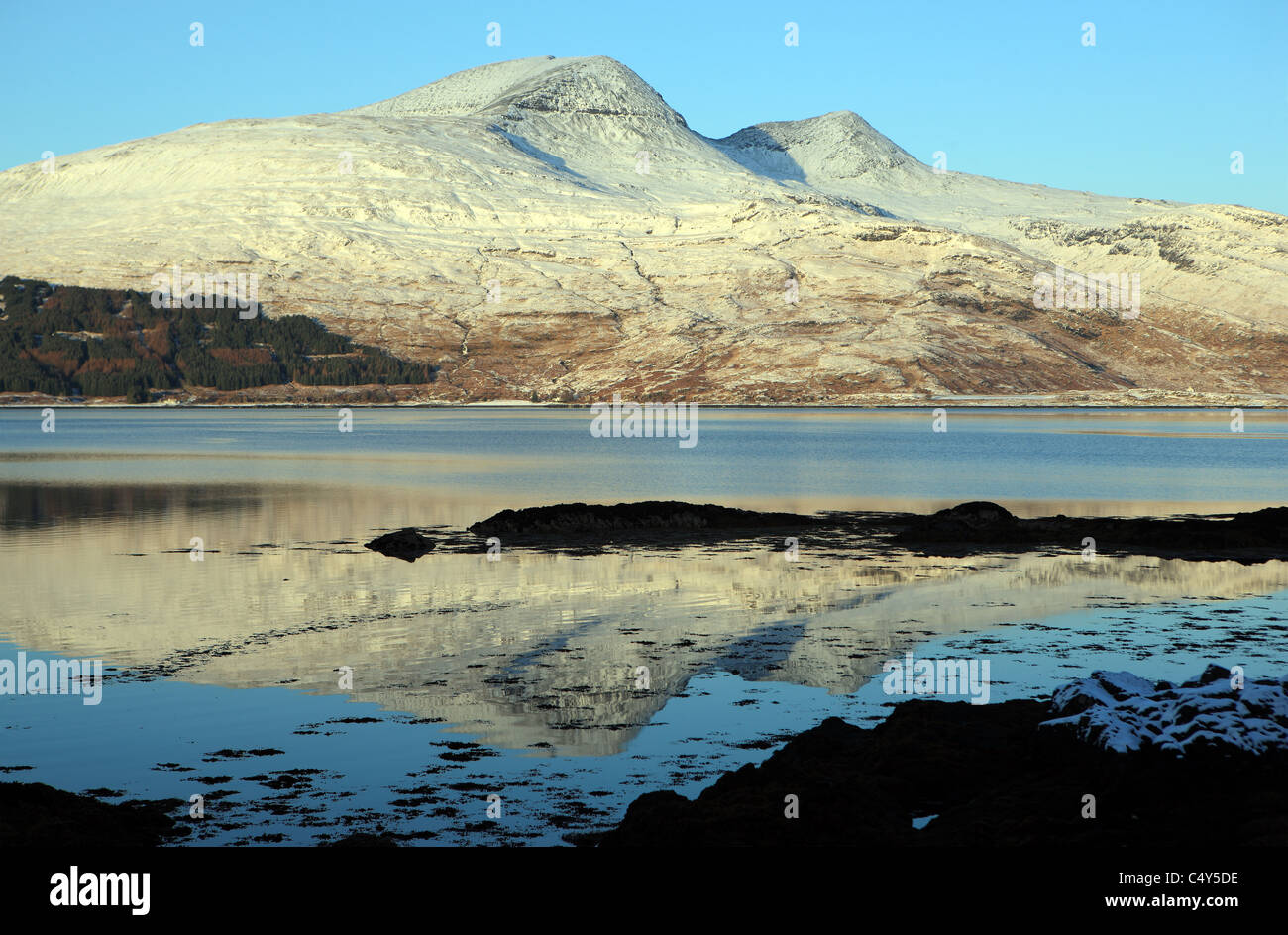 Reflection of Ben More and A'Chioch covered in snow in Loch Scridain on the Isle of Mull - Stock Image