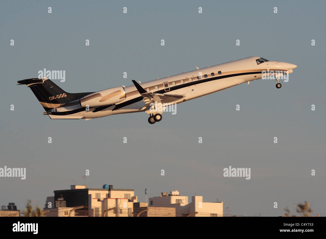 Embraer Legacy 600 business jet taking off at sunset - Stock Image