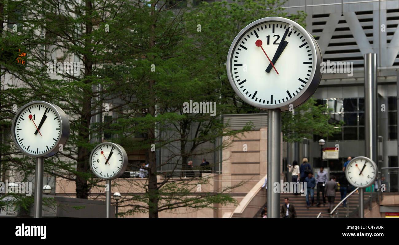 Four clocks at London's Canary Wharf - Stock Image