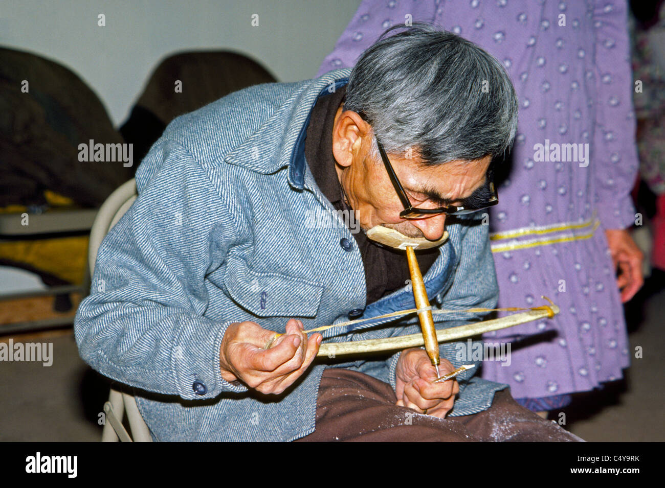 An elderly Eskimo artist demonstrates the use of a native hand tool called a bow drill to make designs in a small - Stock Image
