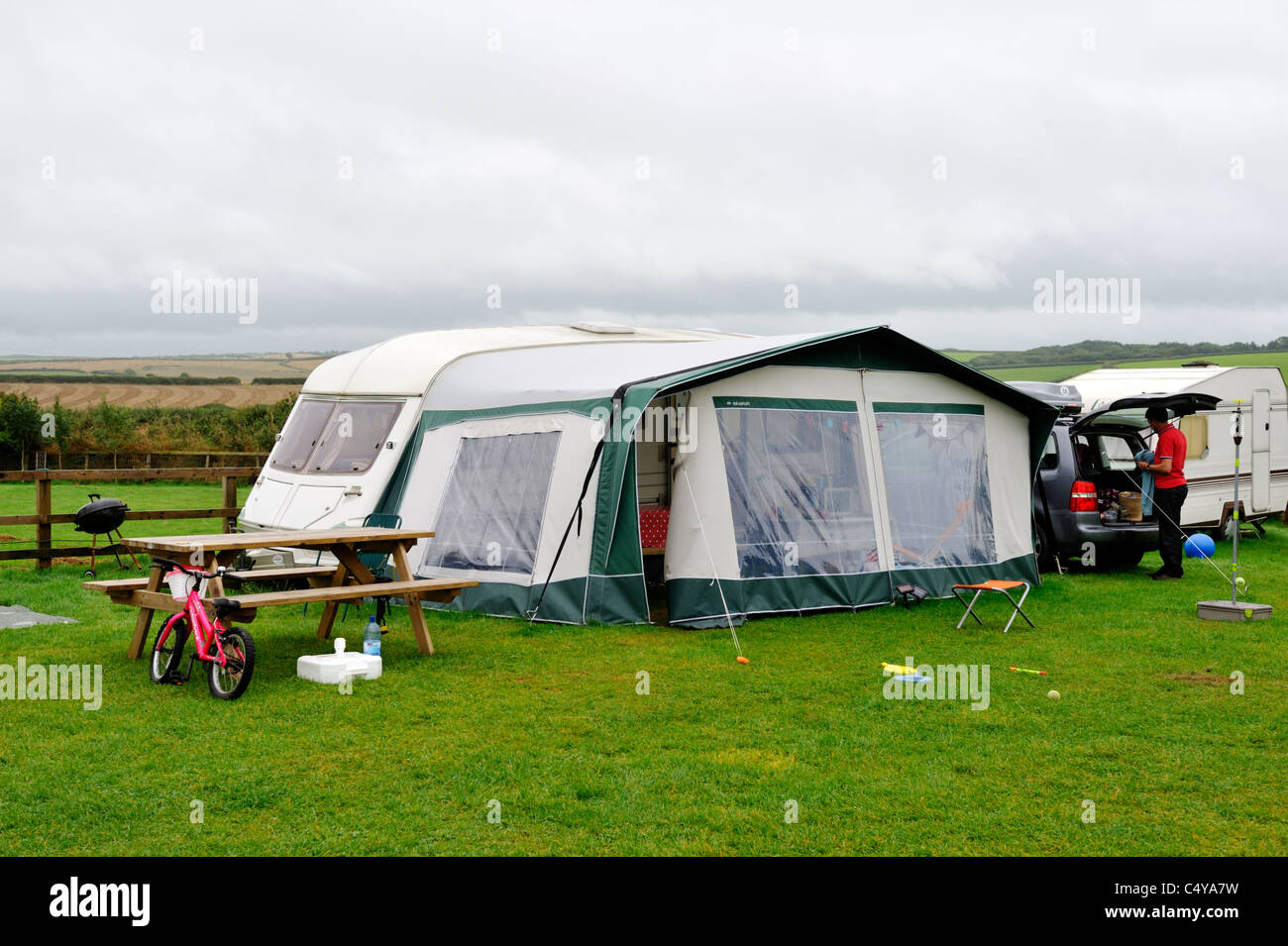 Overcast day camping with caravan in field, north Cornwall - Stock Image