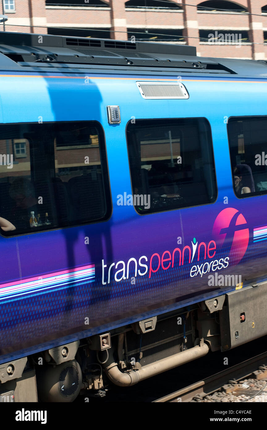Transpennine Express train waiting at a railway station in England. - Stock Image