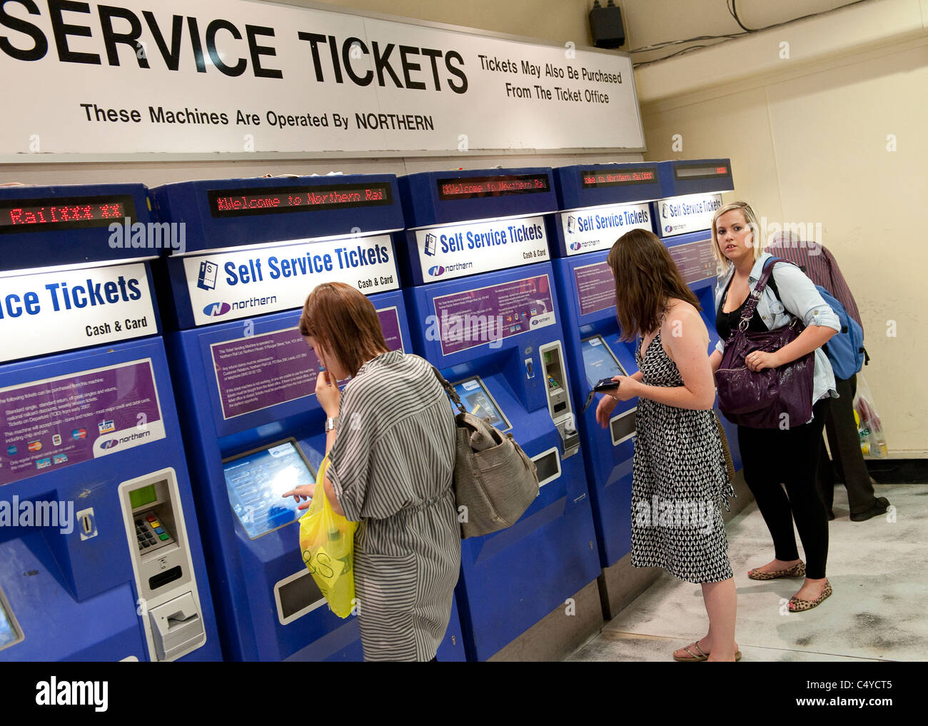 Passengers buying tickets from automated ticket machines at Leeds railway station, England. Stock Photo