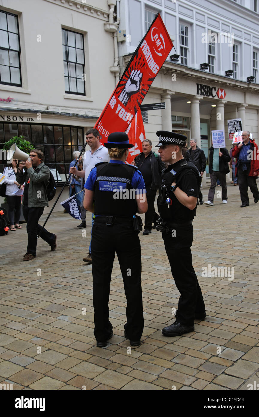 Police officers on duty as Trade Unionists protesting against public service cuts march in Winchester on the Upper - Stock Image
