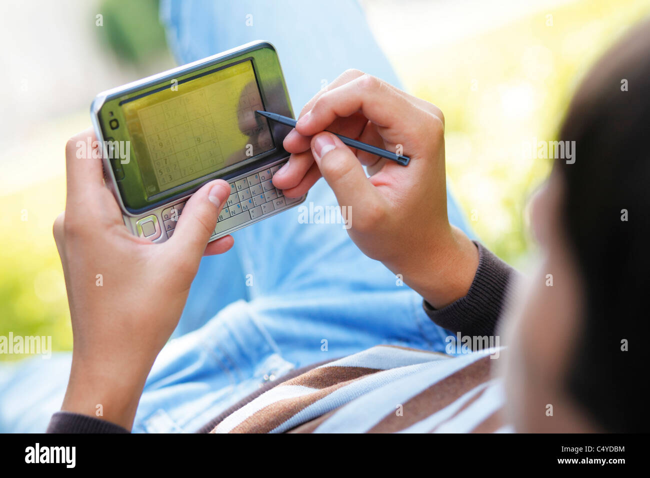 Male hand with digitized pen, touching the screen of a PDA. - Stock Image