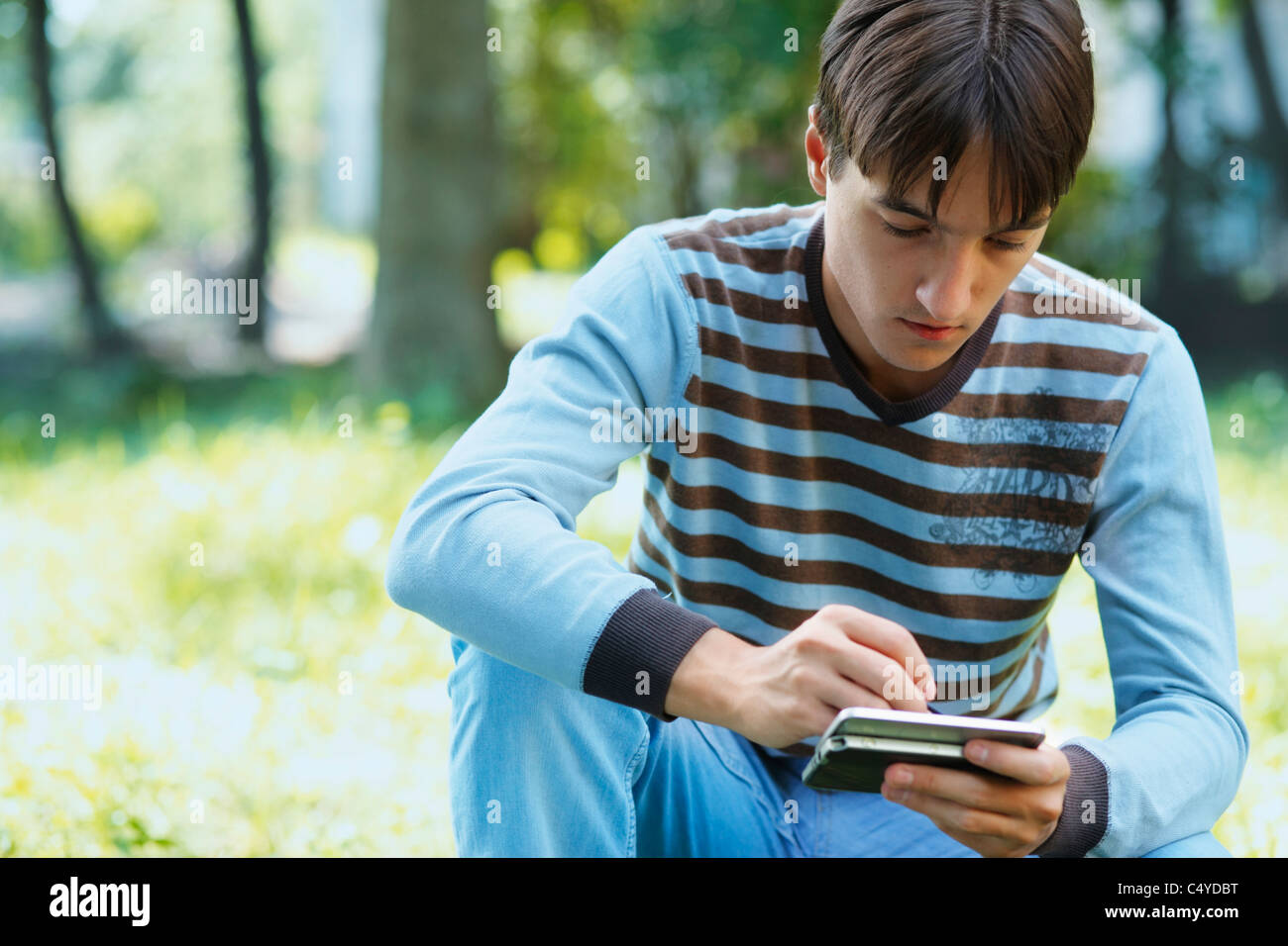 Young man with his PDA in the meadow - Stock Image