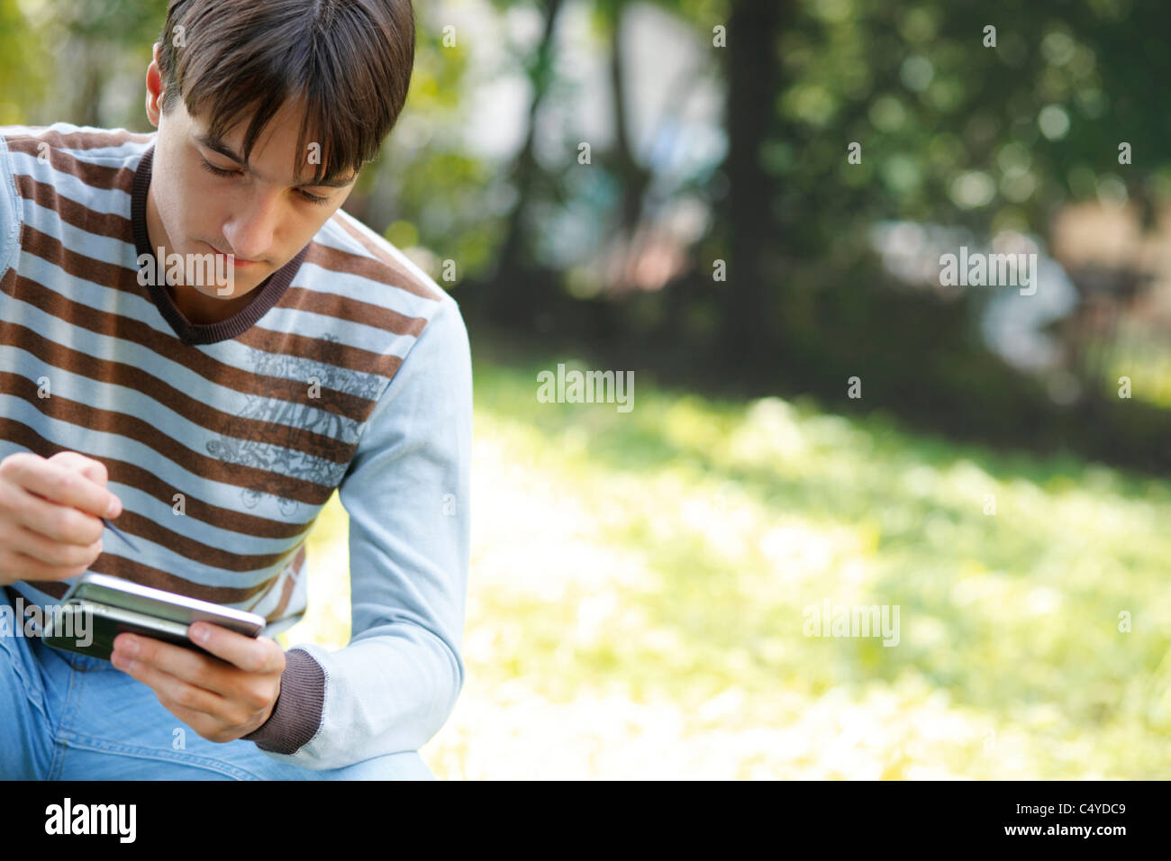 Young man using a PDA outdoors - Stock Image