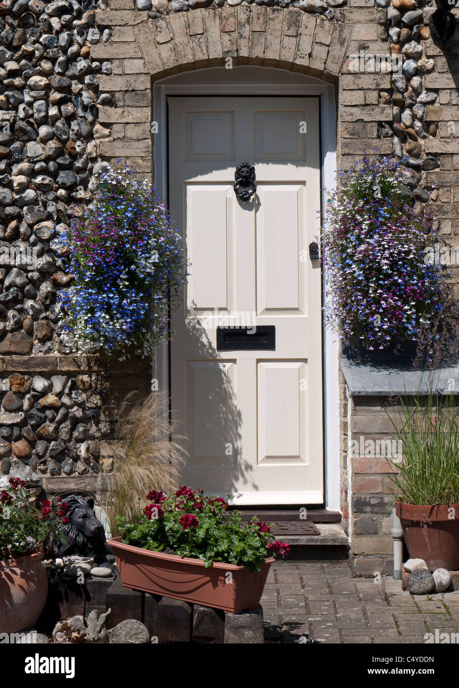 Doorway of stone cottage with summer hanging baskets, England - Stock Image
