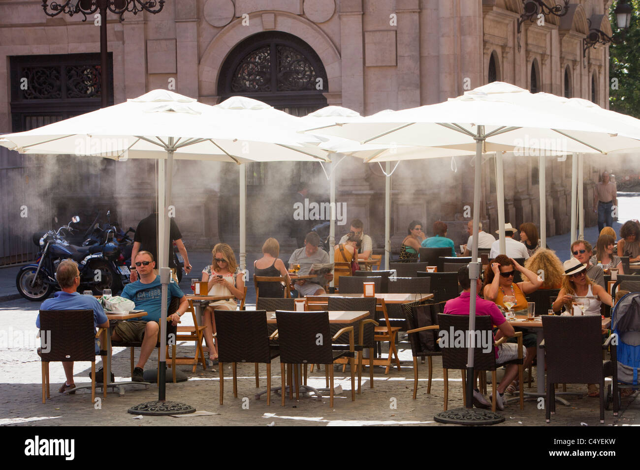 A pavement cafe is using mist sprayers to try to cool customers down in Seville Spain. - Stock Image