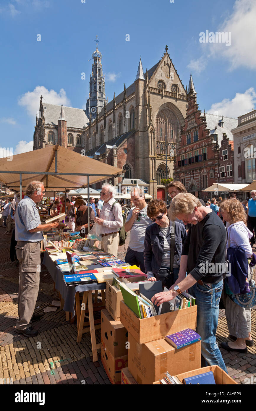 Shoppers at bookstall in the Grote Markt or market place and Sint Bavo church Haarlem, North Holland, Netherlands. Stock Photo