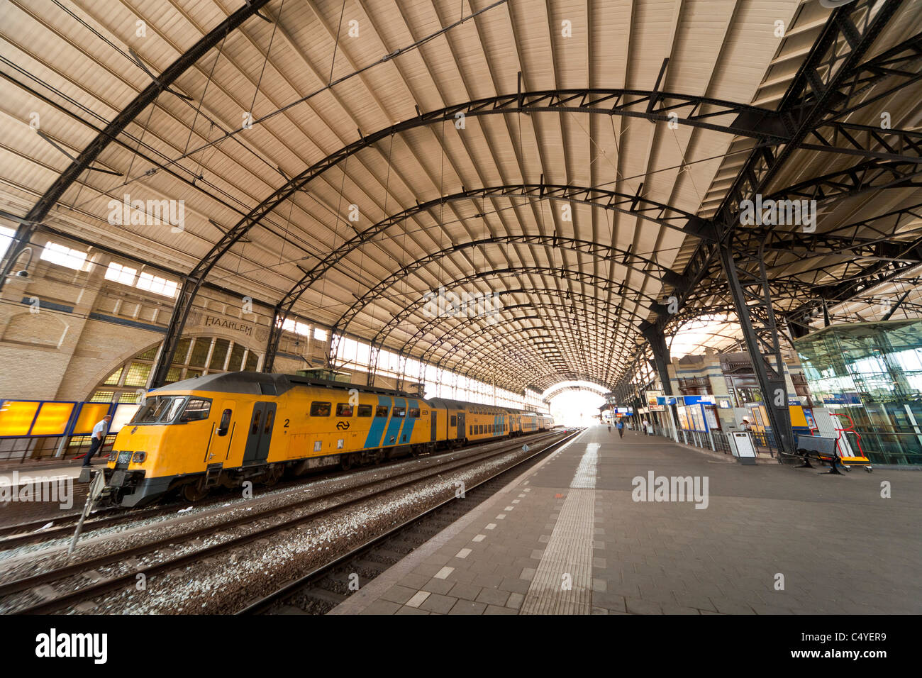 Landscape image of Haarlem Railway Station, Haarlem, Holland, Netherlands with train standing at platform. JMH5058 - Stock Image