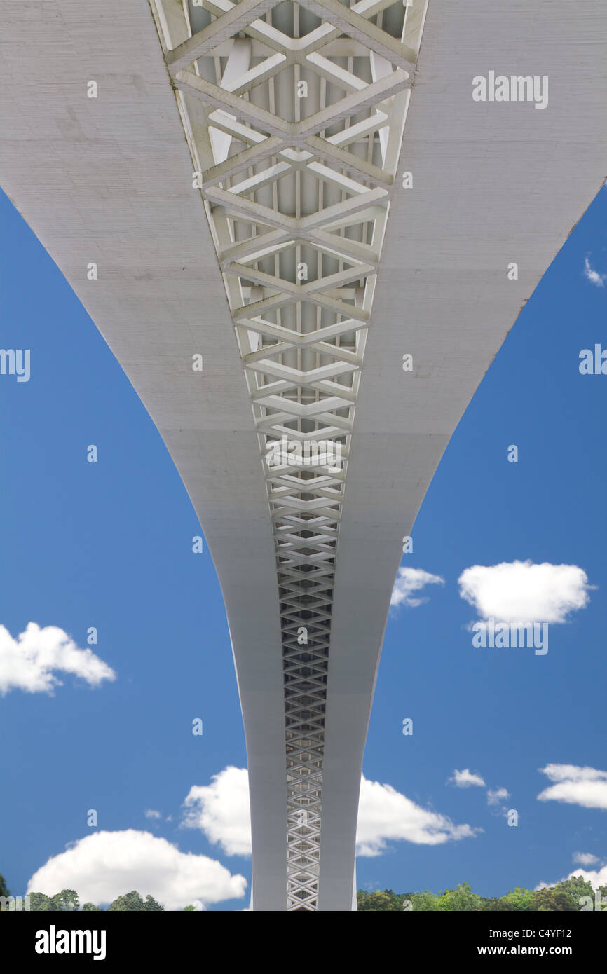 underside of a geometrical concrete bridge with shows a lacing fastening pattern against a blue sky - Stock Image