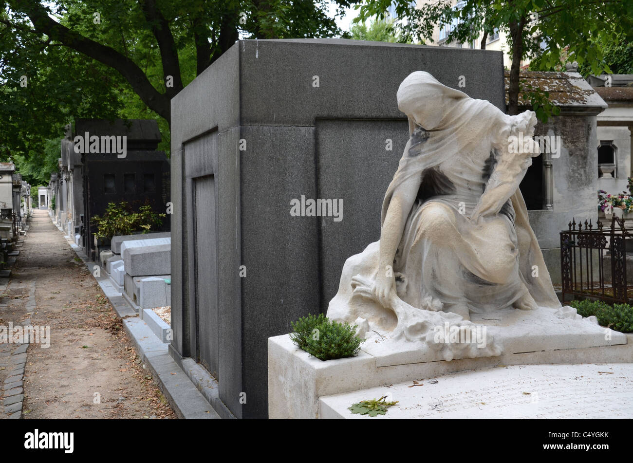 The statue of a woman in mourning lays flowers on a grave in Montmartre Cemetery, Paris, France. - Stock Image