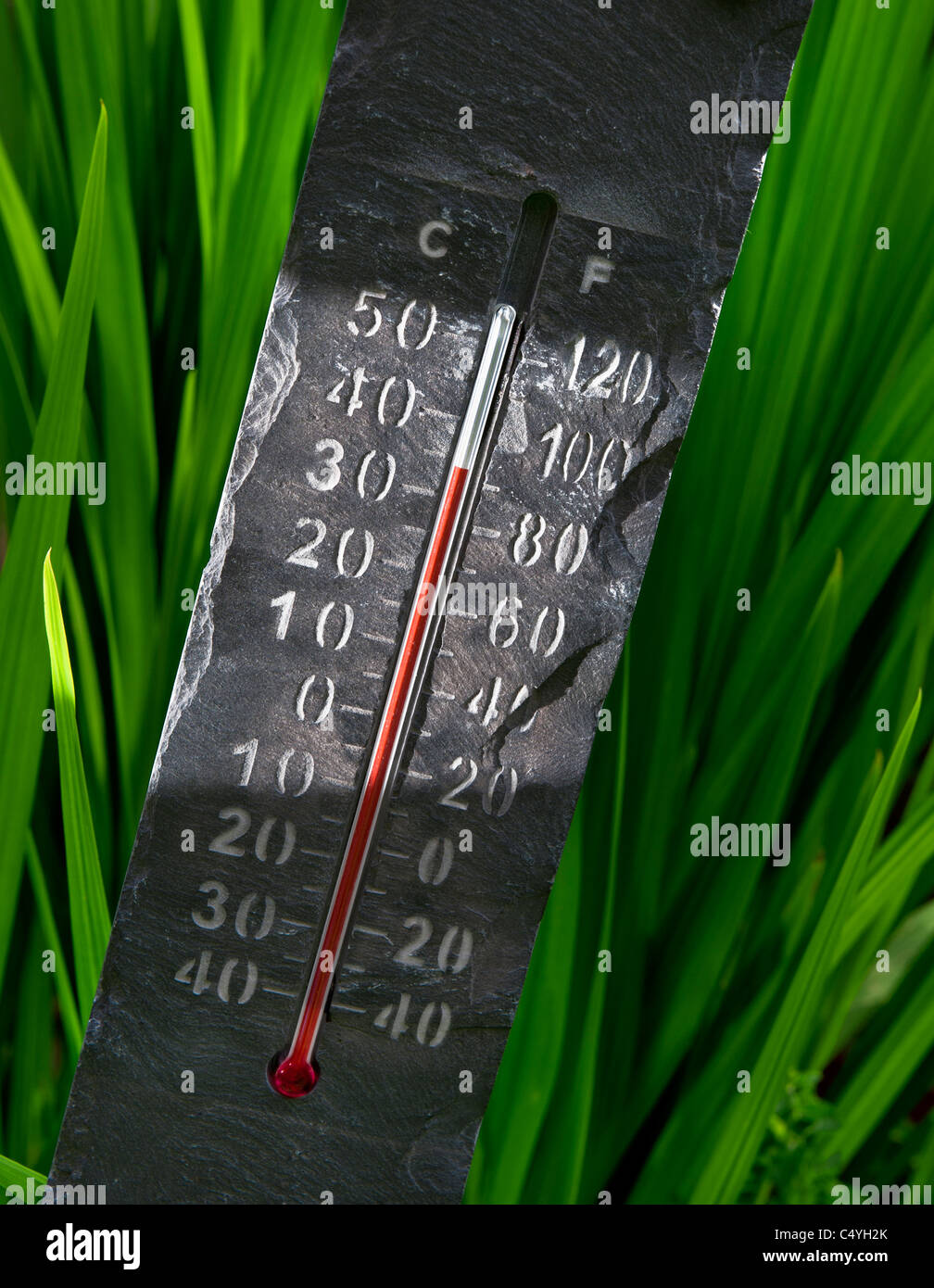 Sunlit stone carved thermometer at 35C 'set in stone' - Stock Image