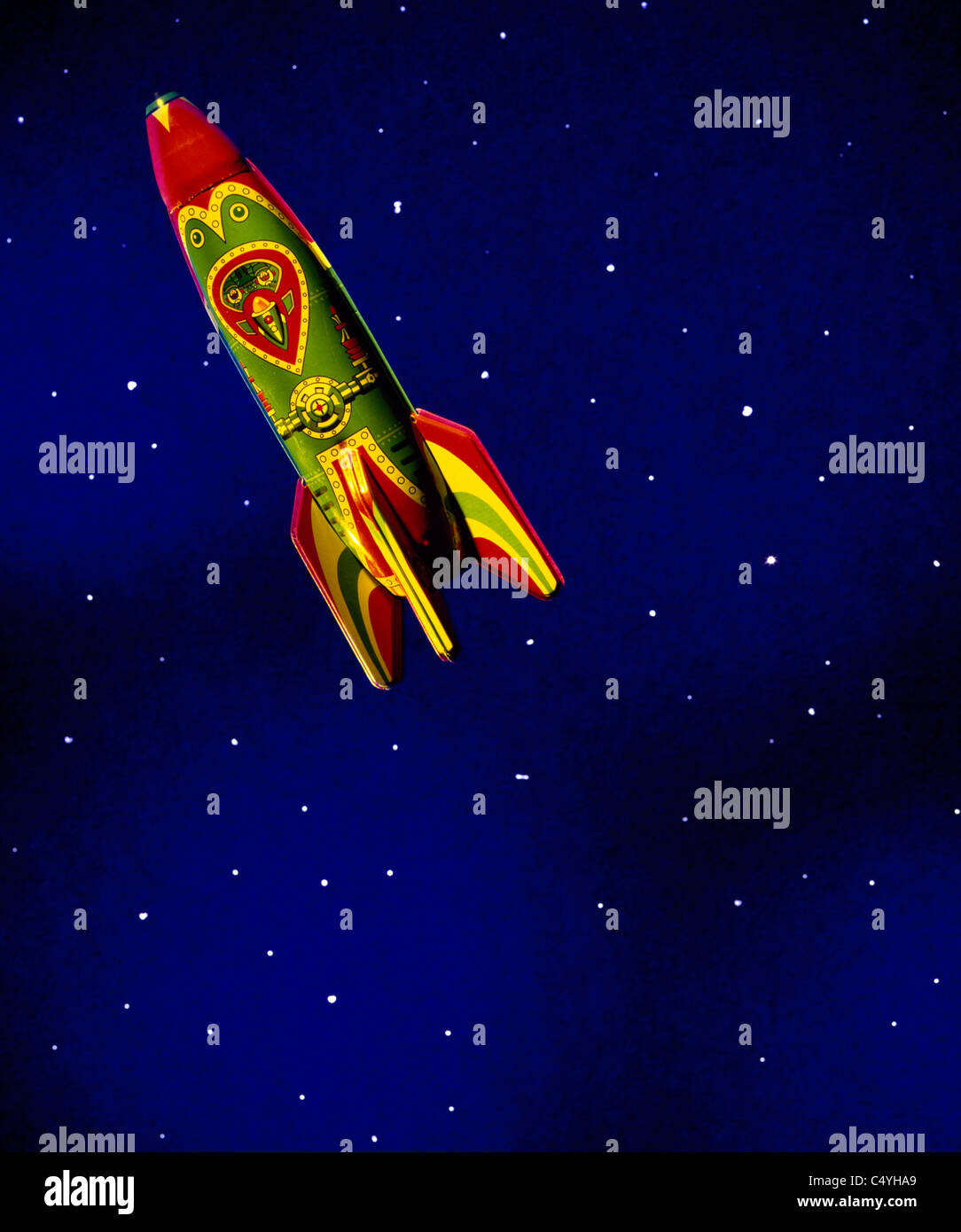 A children's toy rocket ship floating in dark blue space and stars - Stock Image