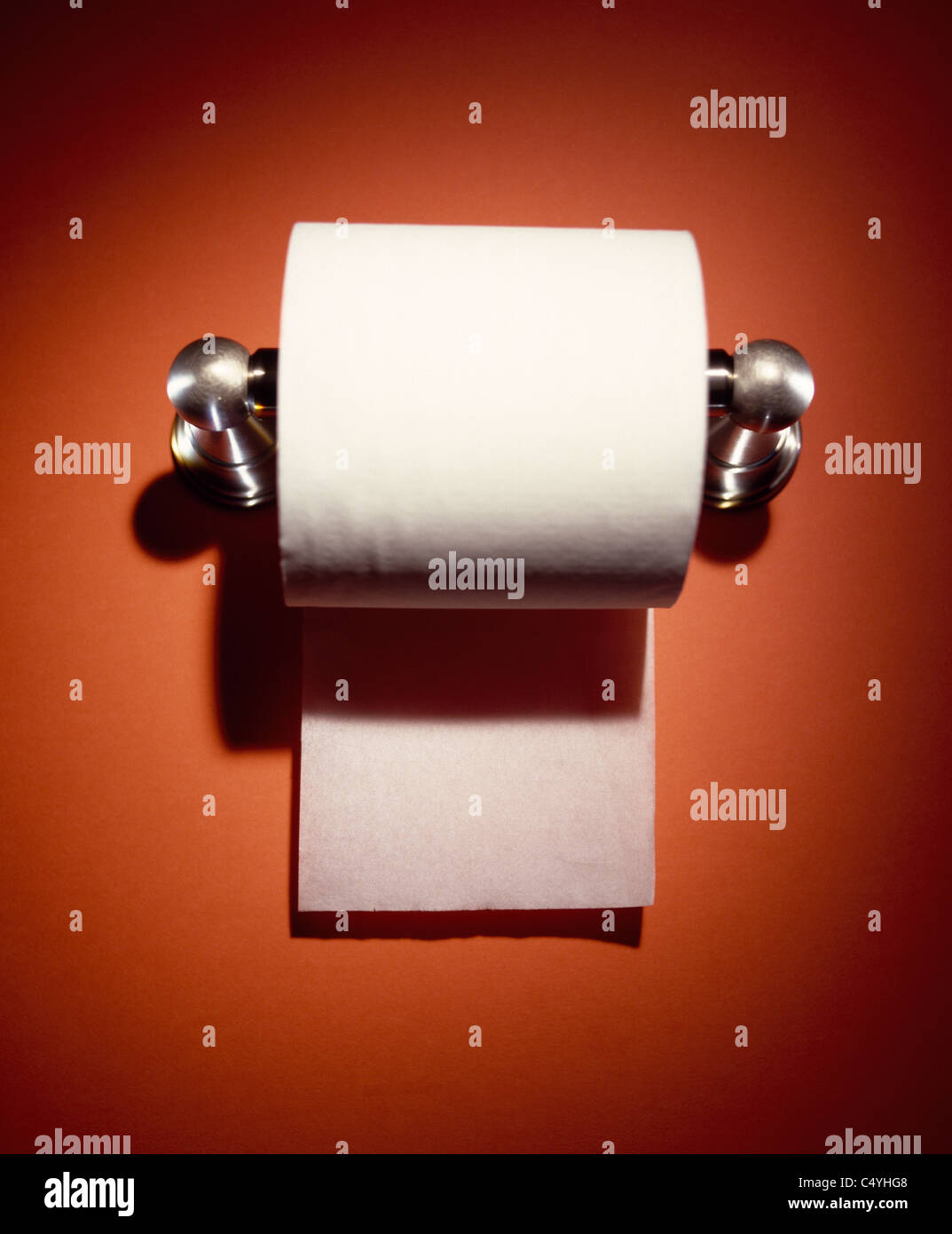 A spotlight on a toilet paper holder and paper roll - Stock Image