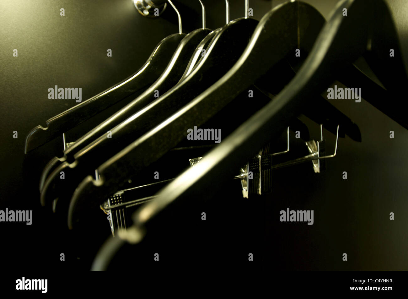 A group of empty black clothing hangers in a closet. - Stock Image
