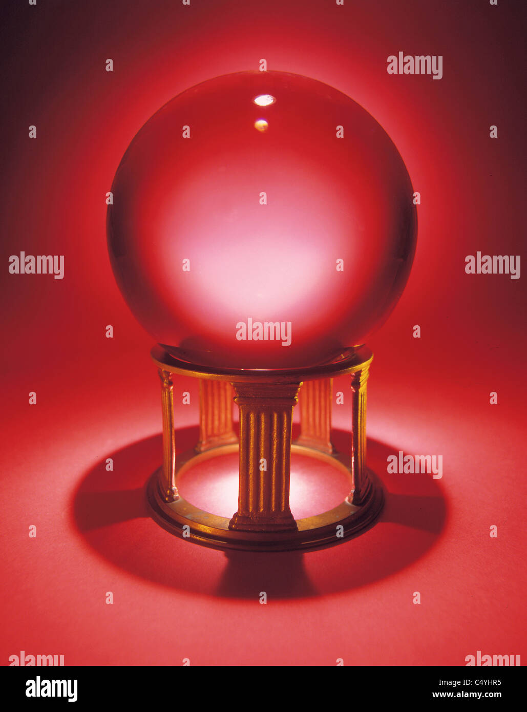 A crystal ball on a small metal stand, glowing red with a shadow. - Stock Image