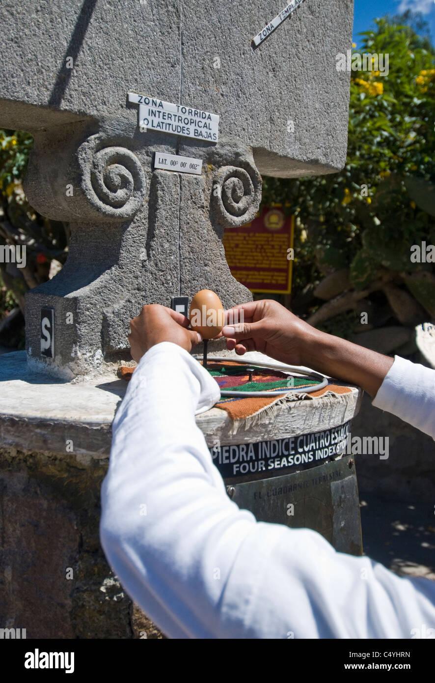 Man balancing an egg on a nail head on the equator near Quito Ecuador - Stock Image