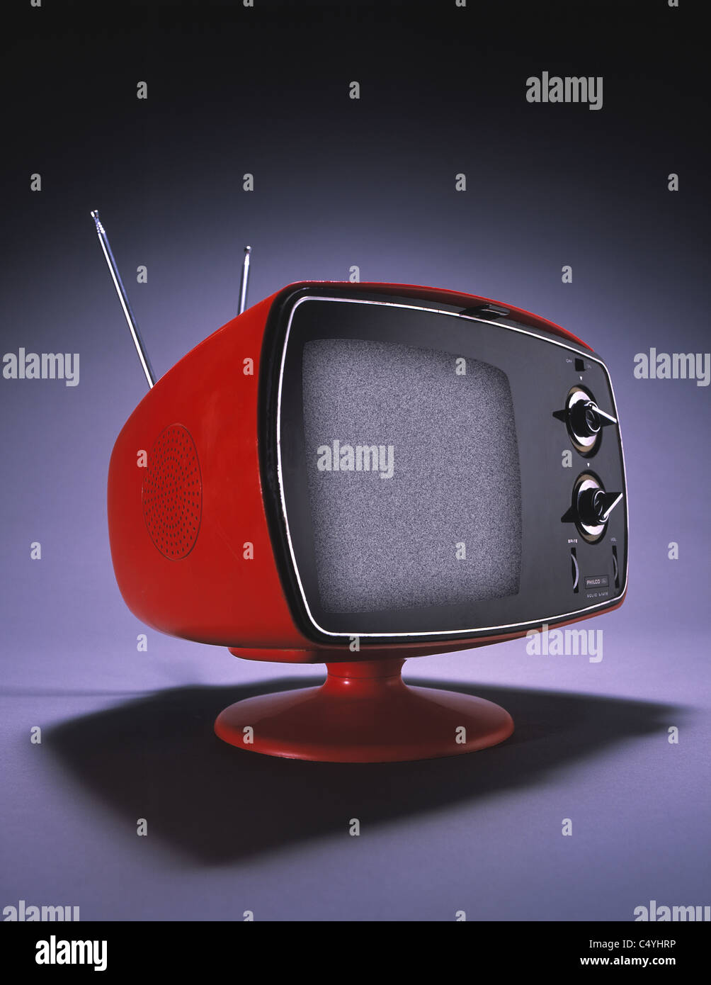 A small orange television set with an antenna and large dials. - Stock Image