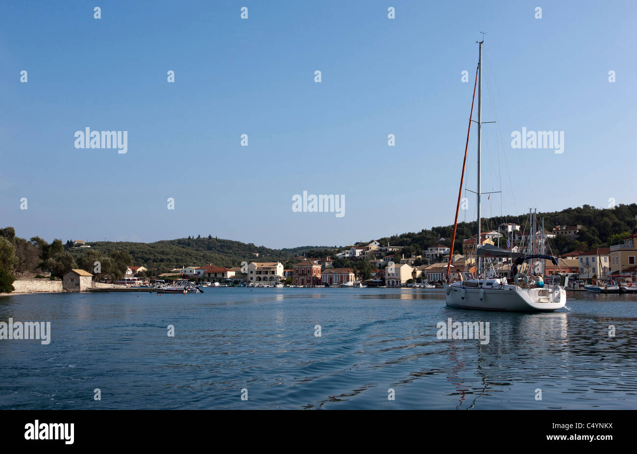 A sailing yacht enter Gaios harbour to moor up for the evening. Paxos, Greece. - Stock Image