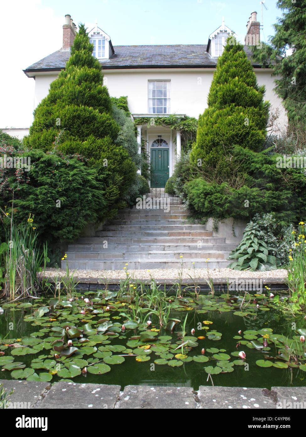 Mature garden with stone steps leading to a Georgian house, a pond in the foreground - Stock Image
