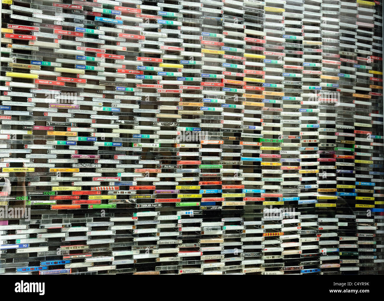 A wall of music cassette tapes lined up against a window forming a creative visual image. - Stock Image
