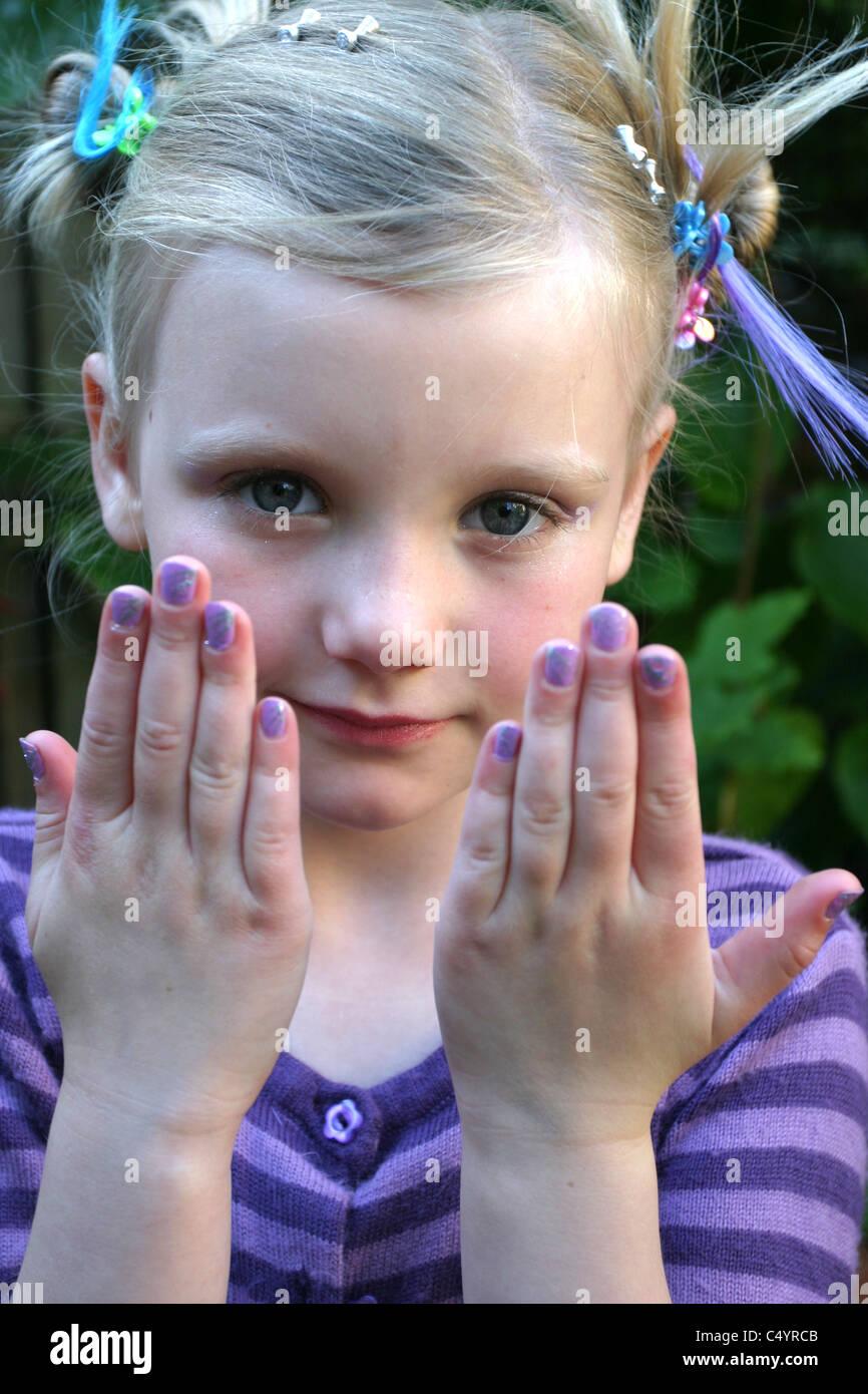 Young Girl wearing Purple Nail Varnish - Stock Image