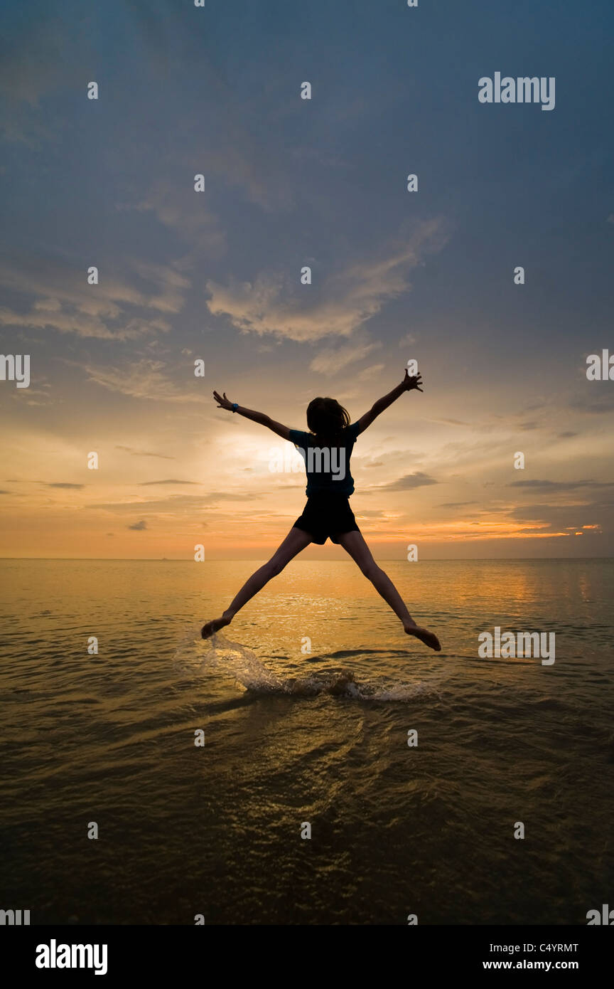 A young woman doing a star jump, jumping for joy and enjoying her freedom on the beach at sunset. - Stock Image
