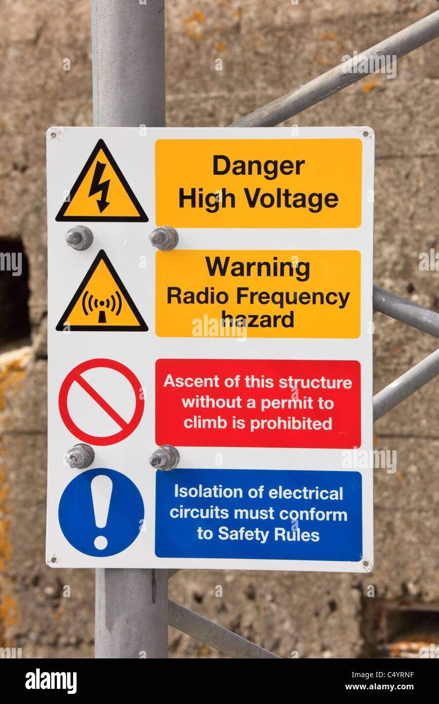 Warning sign with symbols for dangerous high voltage and radio frequency hazard on radio mast - Stock Image