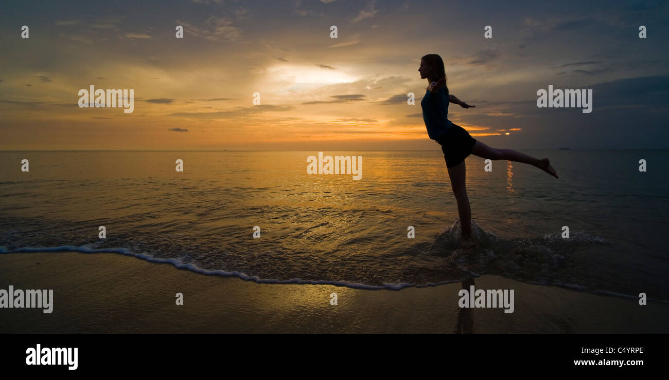 A panorama of a young woman on the beach at sunset practising yoga positions. Taken on Phra Ae Beach, Koh Lanta, - Stock Image