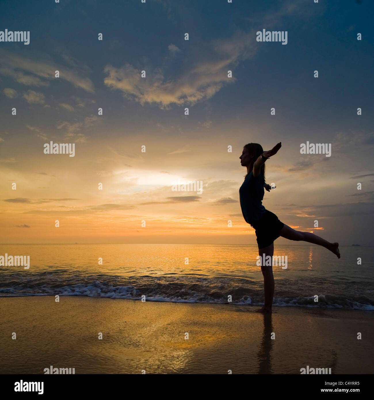 A young woman doing yoga exercises on the beach at sunset.Taken on Phra Ae Beach (Long Beach), Koh Lanta (Lanta - Stock Image